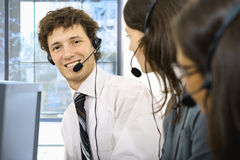 Operators taliking on headset. Young customer service representatives sitting in a row and talking on headset, smiling. Selective focus is placed on man Stock Photography