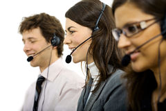 Operators taliking on headset. Young customer service representatives sitting in a row and talking on headset, smiling. Isolated on white background Royalty Free Stock Images