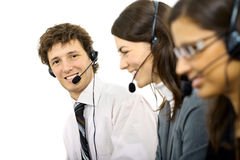 Operators taliking on headset. Young customer service representatives sitting in a row and talking on headset, smiling. Isolated on white background Royalty Free Stock Image