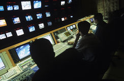 Operatörer i centralt kontrollrum på TV-station Royaltyfri Bild