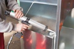 Operazione della pistola del sigillante del silicone Immagini Stock