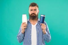 Operi la giusta scelta Pantaloni a vita bassa barbuti dell'uomo scegliere il gel della doccia o dello sciampo Cura di capelli e t fotografie stock libere da diritti