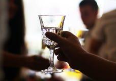 Opgeheven champagneglas bij banket over vergadering stock afbeelding