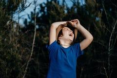 Opgeheven handen die omhoog jongen openlucht in de zomer bos 6 jaar ol glimlachen Royalty-vrije Stock Fotografie