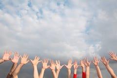 Opgeheven handen op bewolkte hemel Stock Foto