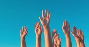 Opgeheven handen tegen blauwe hemel stock videobeelden