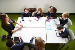 Opgeheven mening van lage schooljonge geitjes die een rond lijst in het klaslokaal met hun vrouwelijke leraar zitten stock fotografie