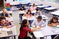 Opgeheven mening van leraar en klasse van basisschooljonge geitjes royalty-vrije stock foto's