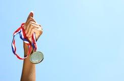Opgeheven vrouwenhand, houdend gouden medaille tegen skyl toekenning en overwinningsconcept Selectieve nadruk Retro Beeld van de  Stock Afbeeldingen