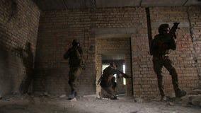 Opgeleide legermilitair die het achtergedeelte van ploeg beveiligen stock videobeelden
