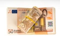 Opgerolde euro met rubber op de vijftig euro bankbiljettenstapel De stapel van de geldbos Stock Afbeelding