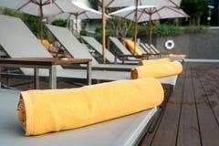 Opgerolde oranje handdoek op een achtergrond van de zonlanterfanter van pool in Re stock foto's