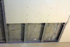 Opgeschort plafond van drywall vast aan metaalkader met schroeven Stock Fotografie