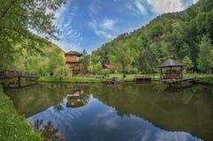 Opgeschort plattelandshuisje dichtbij vijver met klein ponton Stock Foto's