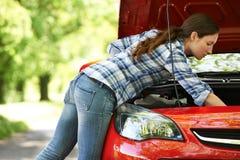 Opgesplitste Vrouwelijke Bestuurder Looking Under Hood Of Car Stock Afbeelding