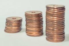 Opgestapelde muntstukken die op een witte achtergrond worden geïsoleerd stock afbeelding