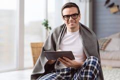 Opgetogen aardige mens die een tablet houden royalty-vrije stock afbeeldingen