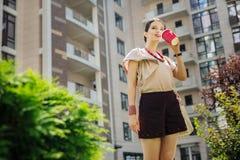 Opgetogen aardige vrouw die van haar koffie genieten royalty-vrije stock afbeelding