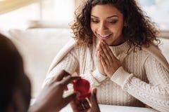 Opgetogen Afrikaanse Amerikaanse vrouw die het voorstel in de koffie ontvangen stock foto