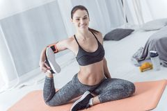 Opgetogen blije vrouw die op een yogamat uitwerken stock afbeelding