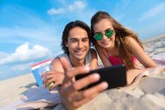 Opgetogen gelukkige vrienden die op het zand rusten Royalty-vrije Stock Foto