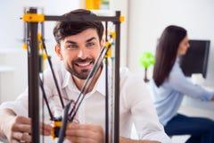 Opgetogen glimlachende mens die 3d printer met behulp van Stock Afbeeldingen