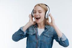 Opgetogen jonge vrouw die favoriet lied zingen stock foto