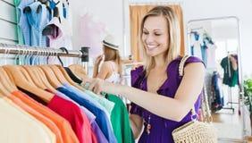 Opgetogen jonge vrouw die kleren kiest Stock Foto's