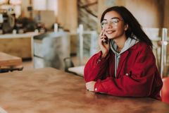 Opgetogen jonge vrouw die op telefoon met genoegen spreken royalty-vrije stock afbeelding
