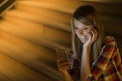 Opgetogen jonge vrouw die sms op haar mobiele telefoon lezen die met opwinding bij het goede nieuws glimlachen aangezien zij zich stock foto's