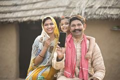 Opgetogen landelijke familie die nieuwe mobiele telefoon houden stock afbeeldingen