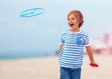 Opgetogen leuke jonge jongen, jong geitje die pret die op zandig strand hebben, de spelen van de vrije tijdsactiviteit met propel Royalty-vrije Stock Afbeelding