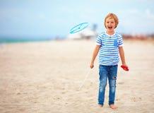 Opgetogen leuke jonge jongen, jong geitje die pret die op zandig strand hebben, de spelen van de vrije tijdsactiviteit met propel Stock Fotografie