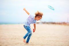 Opgetogen leuke jonge jongen, jong geitje die pret die op zandig strand hebben, de spelen van de vrije tijdsactiviteit met propel Stock Afbeelding