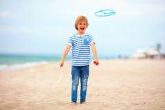 Opgetogen leuke jonge jongen, jong geitje die pret die op zandig strand hebben, de spelen van de vrije tijdsactiviteit met propel Royalty-vrije Stock Fotografie