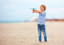 Opgetogen leuke jonge jongen, jong geitje die pret die op zandig strand hebben, de spelen van de vrije tijdsactiviteit met propel Stock Foto's
