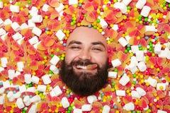 Opgetogen mens die in snoepjes liggen Royalty-vrije Stock Foto