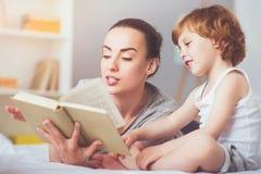 Opgetogen moeder die een fairytale lezen aan haar zoon royalty-vrije stock fotografie