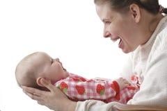 Opgetogen moederbesprekingen aan glimlachende baby Royalty-vrije Stock Afbeeldingen