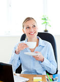 Opgetogen onderneemster het drinken koffie op het werk Stock Afbeelding