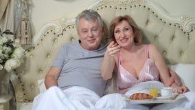 Opgetogen oud paar die op een film thuis letten stock videobeelden