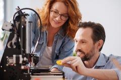 Opgetogen positieve mens die een 3d printerdetail houden Royalty-vrije Stock Fotografie