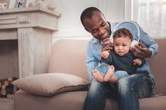 Opgetogen positieve mens die zijn baby houden royalty-vrije stock foto's