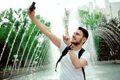 Opgetogen positieve mens in witte t-shirt die vredesgebaar tonen terwijl het nemen van een selfie met een camera dichtbij de font stock foto's