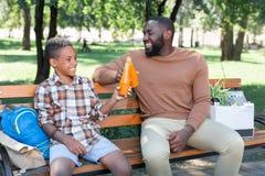 Opgetogen positieve vader en zoon die met dranken toejuichen stock afbeeldingen