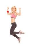 Opgetogen vrouwelijke atleet die uit vreugde springen Stock Fotografie