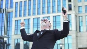 Opgewekt bedrijfsmannetje in kostuum dat succesteken toont dat mobiel, voltooiing houdt stock foto