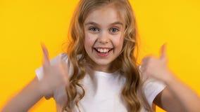 Opgewekt duim-omhoog en meisje die, succesvol gelukkig jong geitje op achtergrond tonen knipogen stock footage