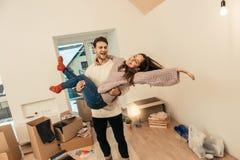 Opgewekt en gelukkig paargevoel terwijl zich het bewegen in nieuw losgemaakt huis royalty-vrije stock foto's