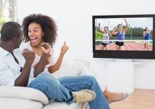 Opgewekt en paar die sporten in televisie toejuichen letten op royalty-vrije stock foto's